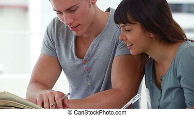 Happy young man helping a friend with her homework