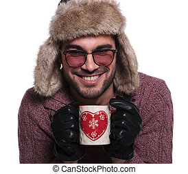 happy young man holding a tea mug and smiles to the camera
