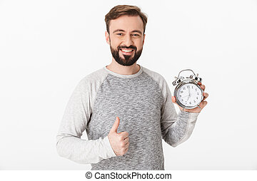 Happy young man holding alarm clock showing thumbs up.