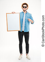 Hapy handsome young man holding blank whiteboard and pointing on it