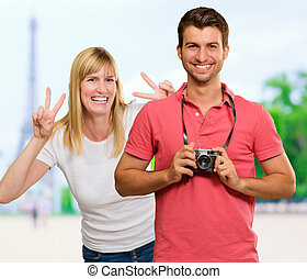 Happy Young Man Holding Camera In Front Of Woman Gesturing