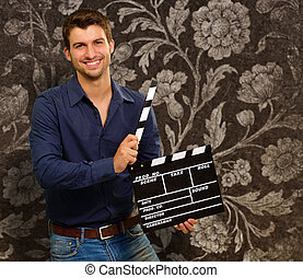 Happy Young Man Holding Clapboard, Indoor