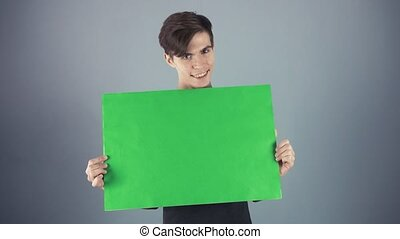 Happy Young man in black shirt holding green key sheet poster gray background