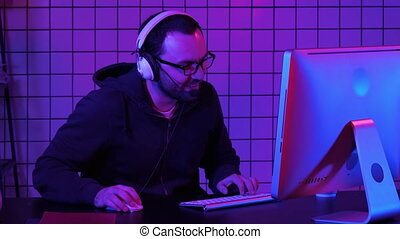 Happy young man in eyeglasses with headset playing and winning computer game.