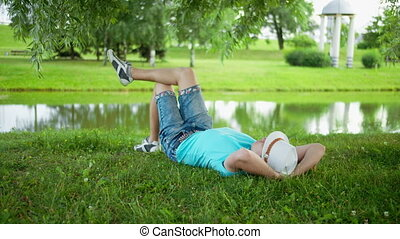 Happy young man in hat resting lying on the grass in city park under a tree