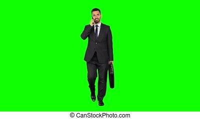 Happy young man in suit talking on smartphone on green background, Chroma key