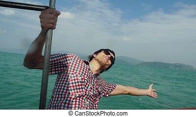 Happy young man in sunglasses enjoying sailing boat on sea...