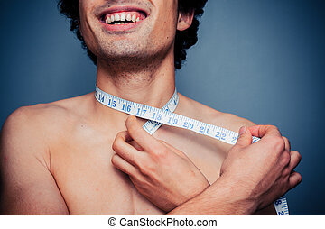Happy young man is measuring his neck
