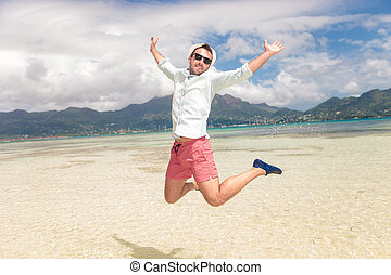 happy young man jumping of joy on the beach