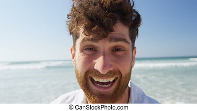Happy young man looking at camera on the beach 4k