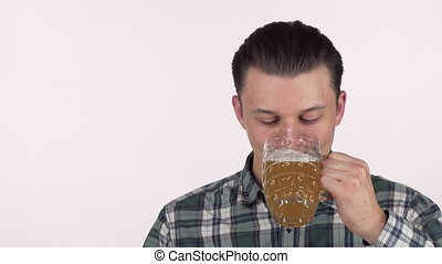 Happy young man looking excited, drinking delicious beer, smiling happily