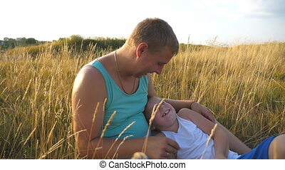Happy young man lying on grass at the field and playing with his baby boy. Cheerful daddy and his child having fun together in a park. Father tickling his little son outdoor. Slow motion Close up