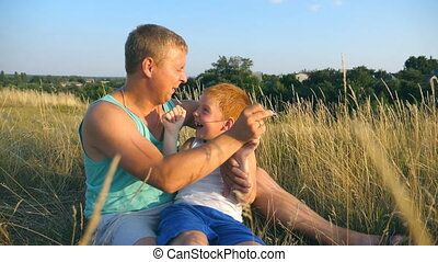 Happy young man lying on grass at the field and playing with his baby boy. Father tickling his little son outdoor. Cheerful daddy and his child having fun together in a park. Slow motion Close up