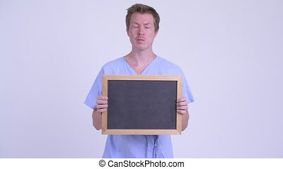 Happy young man patient thinking while holding blackboard