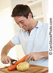 Happy young man peeling vegetable in kitchen