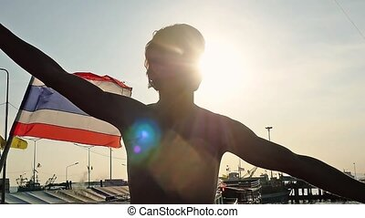Happy young man raises his hands in slow motion on the pier by the sea next to thai flag. The sun is shining with beautiful lens flare effects.