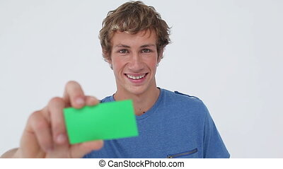 Happy young man showing a business card