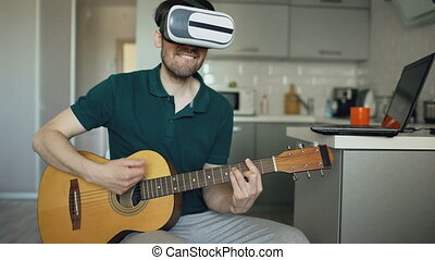 Happy young man sitting at kitchen learning to play guitar...