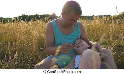 Happy young man sitting on grass at the field and playing with his baby boy. Cheerful daddy and his child having fun together in nature. Father tickling his little son outdoor. Slow motion Close up
