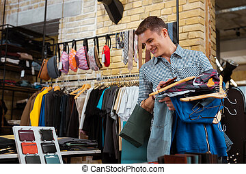 Happy young man smiling and holding clothes while looking at wallets