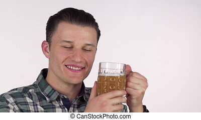 Happy young man smiling with eyes closed, cuddling with a mug of tasty beer