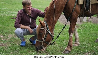 Happy young man smoothes the horse's mane with his hand.