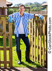 young man standing at garden gate