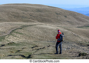 Happy young man standing on mountain. Happy young tourist man with backpack standing on peak and watching mountain road.