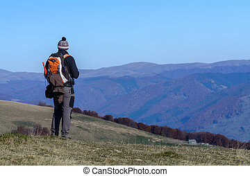 Happy young man standing on mountain. Happy young tourist man with backpack standing on rocky cliff and enjoying panoramic view over afforested mountains.