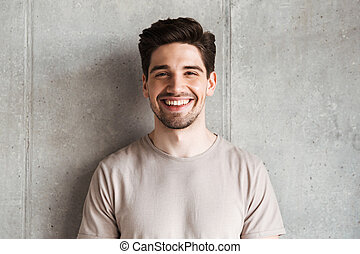 Happy young man standing over grey wall