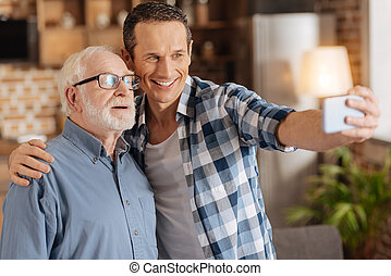 Happy young man taking selfies with his senior father