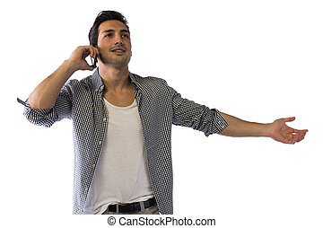 Happy young man talking on cell phone with arms open