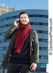 Happy young man talking on cellphone in the city