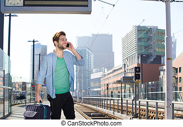 Happy young man talking on mobile phone at train station platform