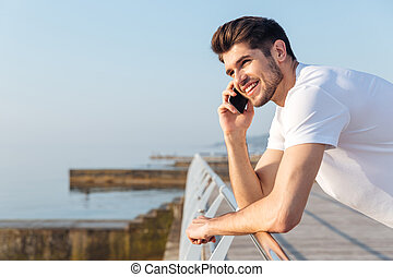 Happy young man talking on mobile phone outdoors - Happy...