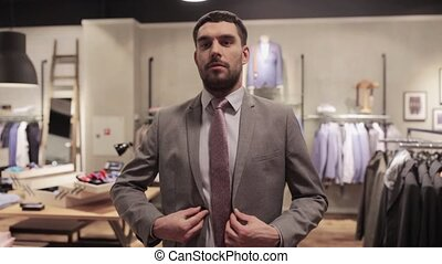 happy young man trying suit at clothing store - sale,...