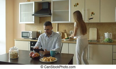 Happy young man using digital tablet computer sitting in the kitchen and talking his wife while she cooking at home