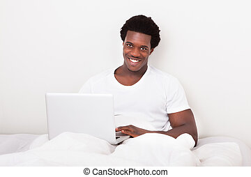 Happy Young Man Using Laptop On Bed
