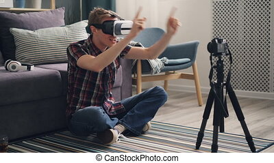 Happy young man male vlogger is sharing his experience with virtual reality glasses recording video for subscribers expressing excitement and joy wearing headset.