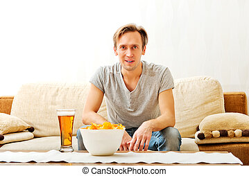 Happy young man watching sports on tv
