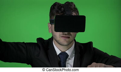 Happy young man wearing formal suit with 3d vr glasses to scroll and type in cyberspace on a green screen background