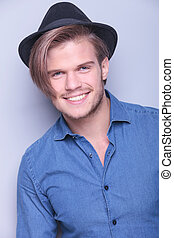 happy young man wearing hat smiles