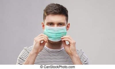 happy young man wearing protective medical mask - health ...