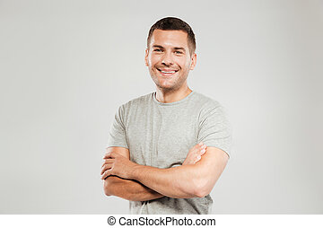 Happy young man with arms crossed. Looking at camera.