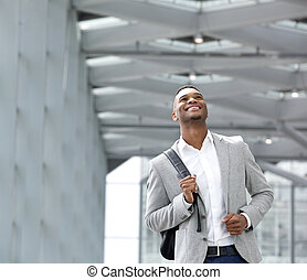 Happy young man with bag at airport