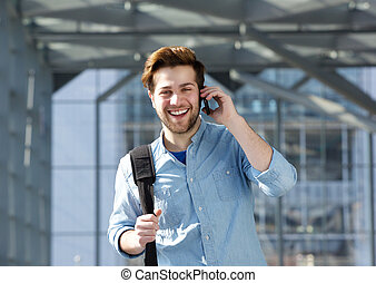 Happy young man with bag talking on cell phone