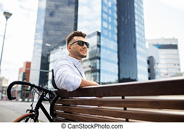 happy young man with bicycle sitting on city bench - people,...