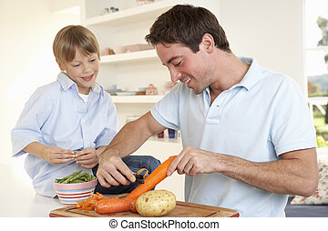 Happy young man with boy peeling vegetables in kitchen