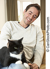 Happy young man with cat sitting on sofa