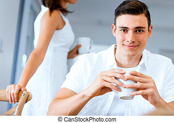 Happy young man with cup of tea or coffee